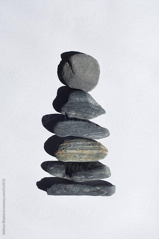 Stones stacked up against a white background. by Shikhar Bhattarai for Stocksy United