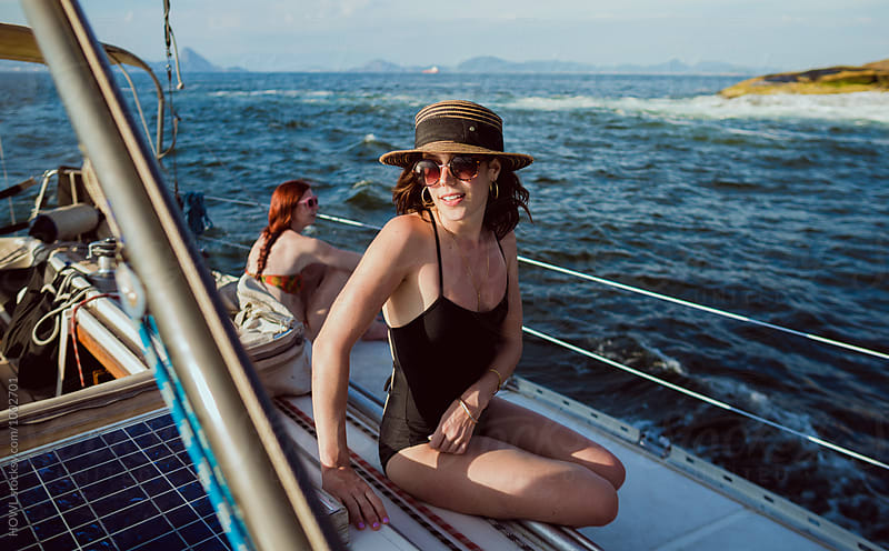 Young woman relaxes in the sun on a summer cruise by HOWL for Stocksy United