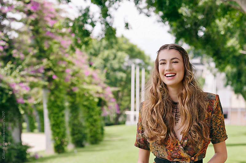 young woman smiling in the park by Gillian Vann for Stocksy United