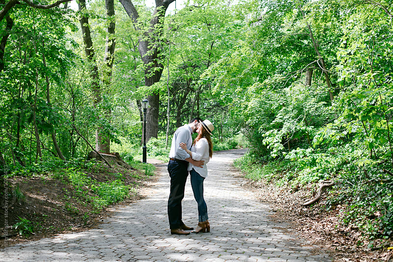 Couple in love flirting on sidewalk in park  by Jen Brister for Stocksy United