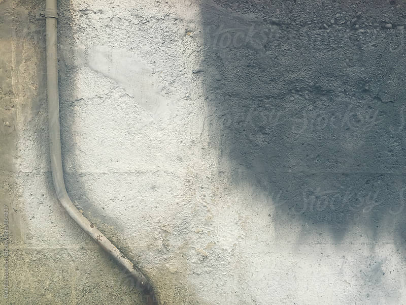 Metal utility pipe and grey paint covering graffiti on concrete wall by Paul Edmondson for Stocksy United