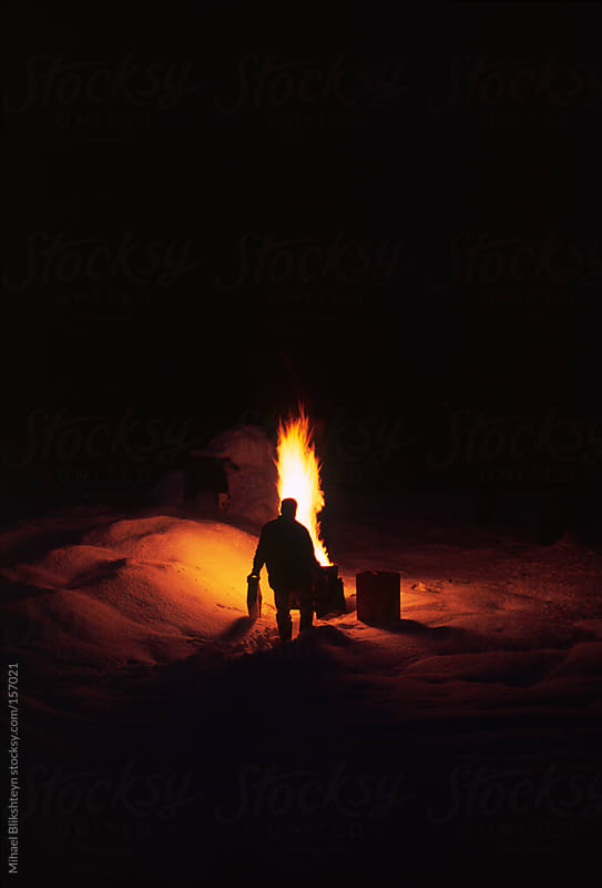 Man making a bonfire in the snow in the winter at night by Mihael Blikshteyn for Stocksy United