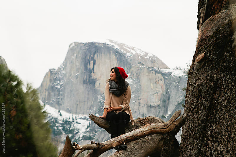young woman sits in tree in yosemite national park by Jesse Morrow for Stocksy United