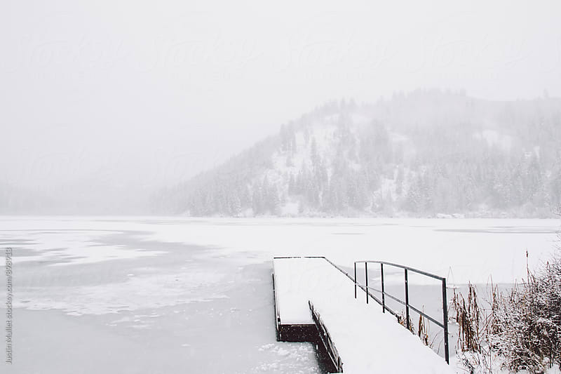 Snow covered dock on a frozen lake shore by Justin Mullet for Stocksy United