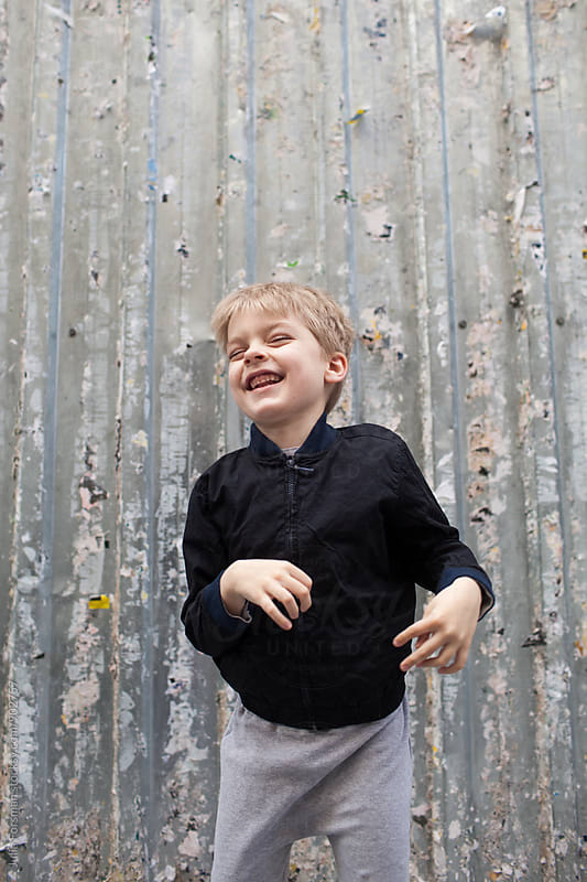 Happy boy in front of urban corrugated metal wall by Julia Forsman for Stocksy United