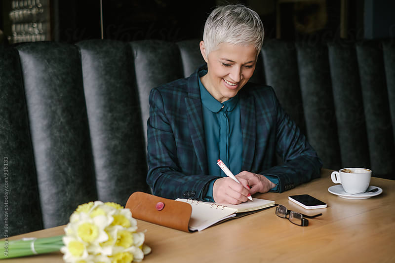 Smiling Senior Businesswoman Writing Notes at the Cafe by Aleksandra Jankovic for Stocksy United