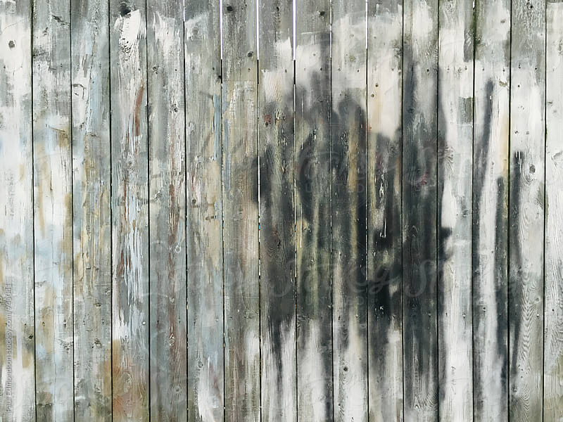 Graffiti paint covering worn wood fence by Paul Edmondson for Stocksy United
