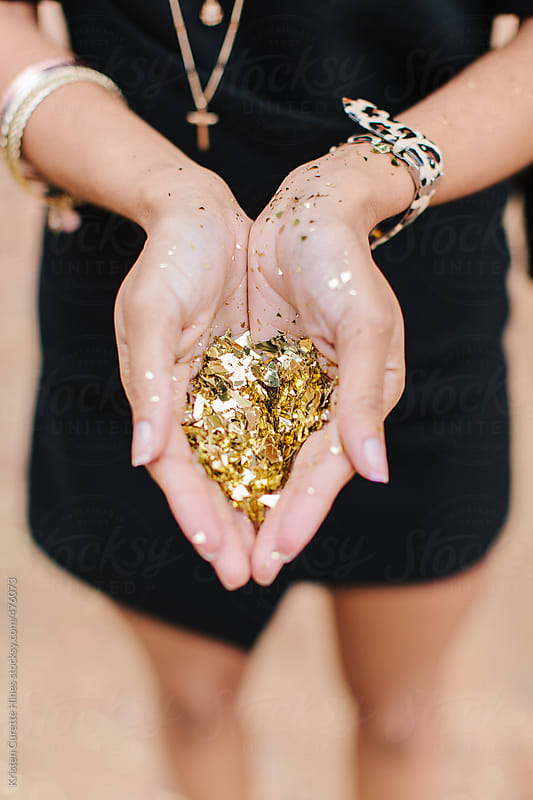 Gold confetti woman hands by Kristen Curette Hines for Stocksy United