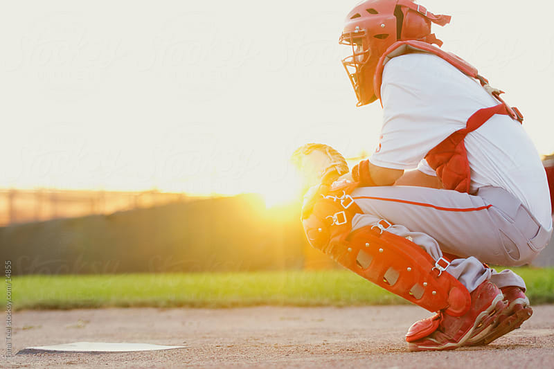 Baseball catcher squatting behind home plate backlit by sun.  by Tana Teel for Stocksy United