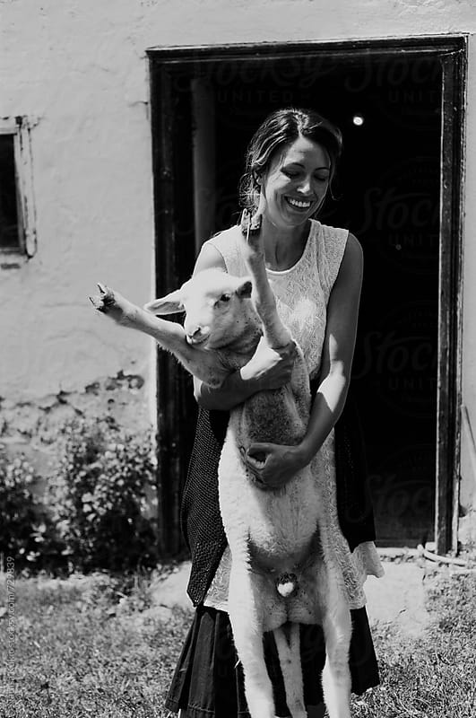 Young woman in the country playing with little lamb by Natasa Kukic for Stocksy United