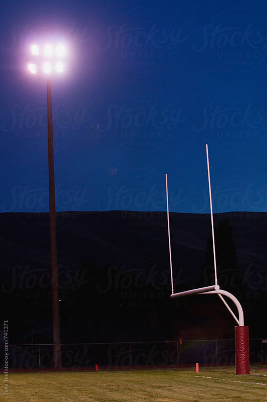 Stadium lights shine over football field goal by Tana Teel for Stocksy United