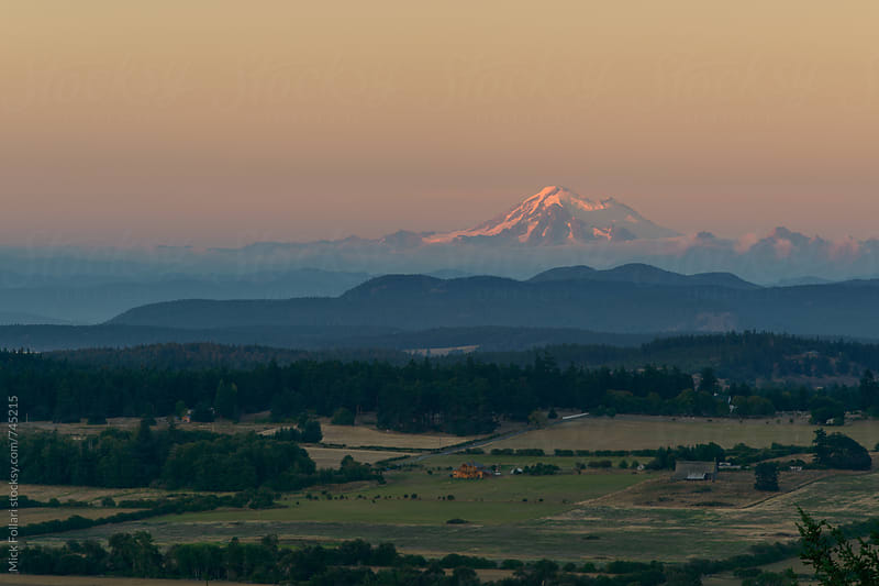 Mt. Baker seen across the bucolic farmland of San Juan Island, WA by Mick Follari for Stocksy United