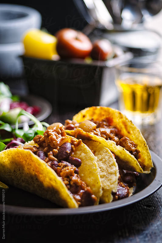 A plate of pork tacos and a beer in the background. by Darren Muir for Stocksy United