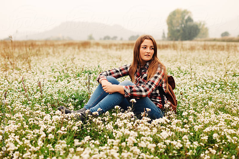 A 14 years old girl sitting in a flowery field in autumn. by BONNINSTUDIO for Stocksy United