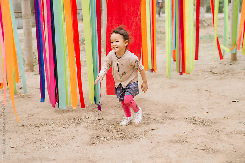 Toddler girl running in ribbon labyrinth by Maa Hoo for Stocksy United