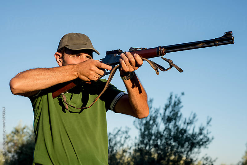 Hunter with a rifle in the countryside, Spain by Bisual Studio for Stocksy United