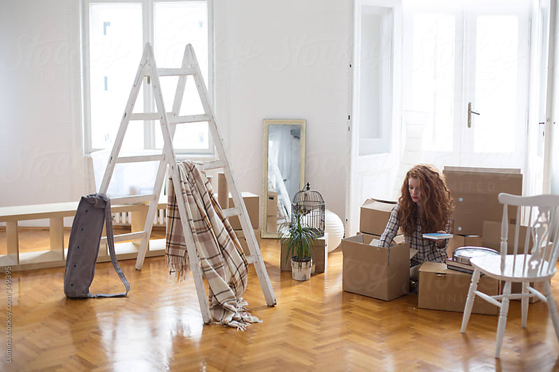 Young Woman Unpacking After Moving In by Lumina for Stocksy United