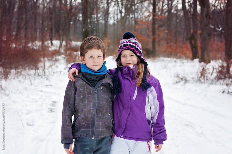 Winter portrait of two friends in the snowy woods standing next to each other by Lea Csontos for Stocksy United