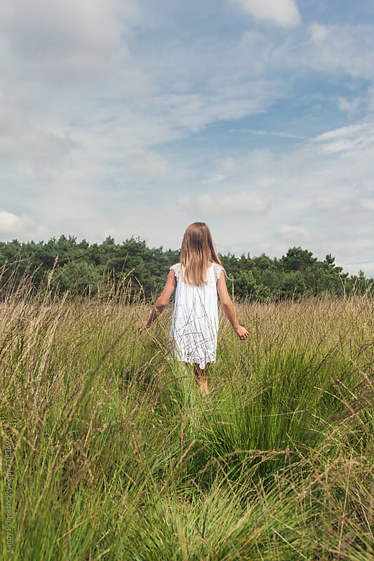 Back of a little girl in a white dress walking through a field by Cindy Prins for Stocksy United