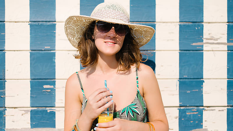 Portrait of a young woman with hat at the beach by Brkati Krokodil for Stocksy United