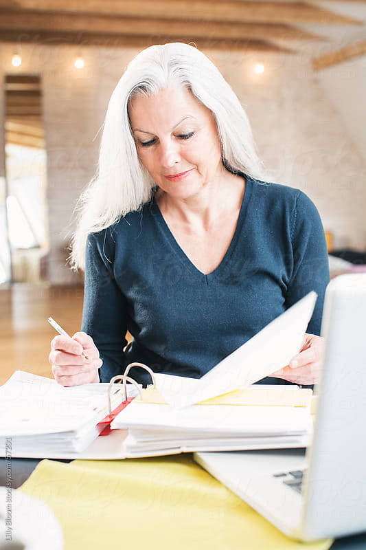 A senior woman doing finances at home, holding a pen, looking at a folder. by Lilly Bloom for Stocksy United