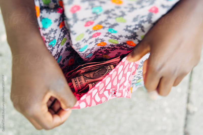 Money in the pocket of a girl's apron by Gabriel (Gabi) Bucataru for Stocksy United