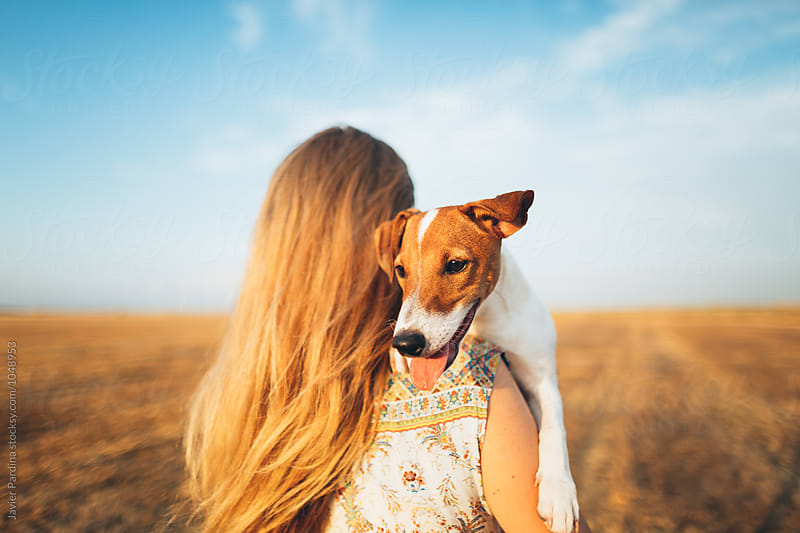 woman with puppy in the hands by Javier Pardina for Stocksy United