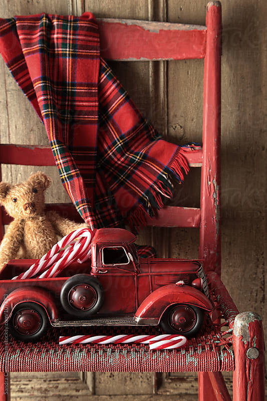 Old toy truck with teddy bear on red chair by Sandra Cunningham for Stocksy United