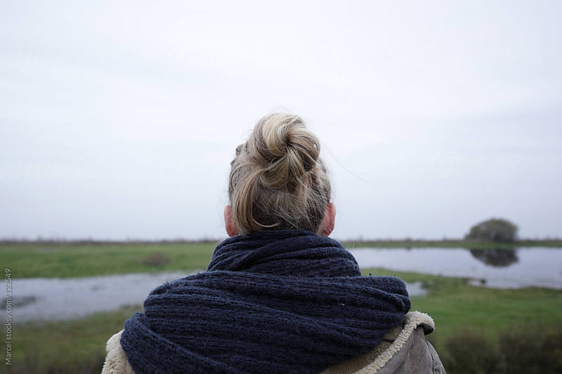 Young woman looking over the wet land by Marcel for Stocksy United