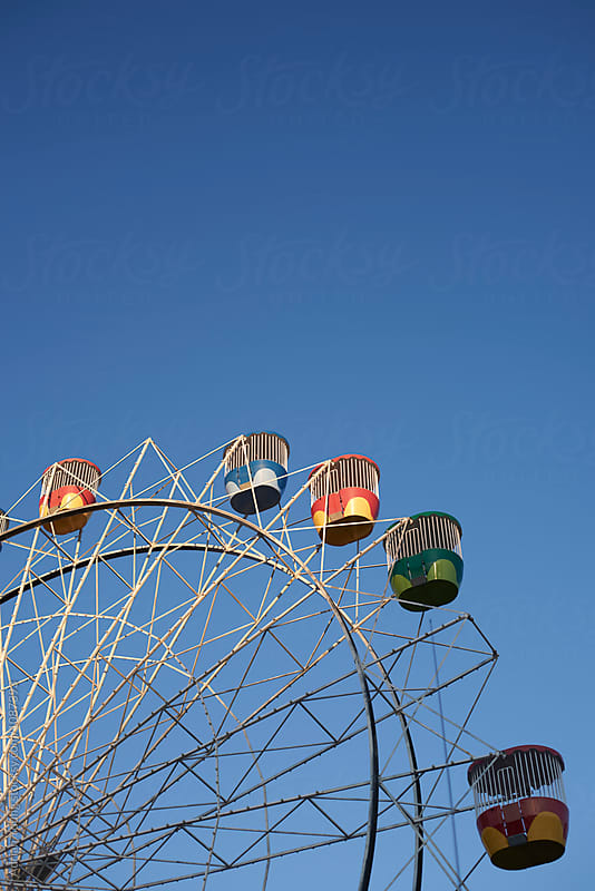Ferris Wheel Against Blue Sky by Adrian P Young for Stocksy United
