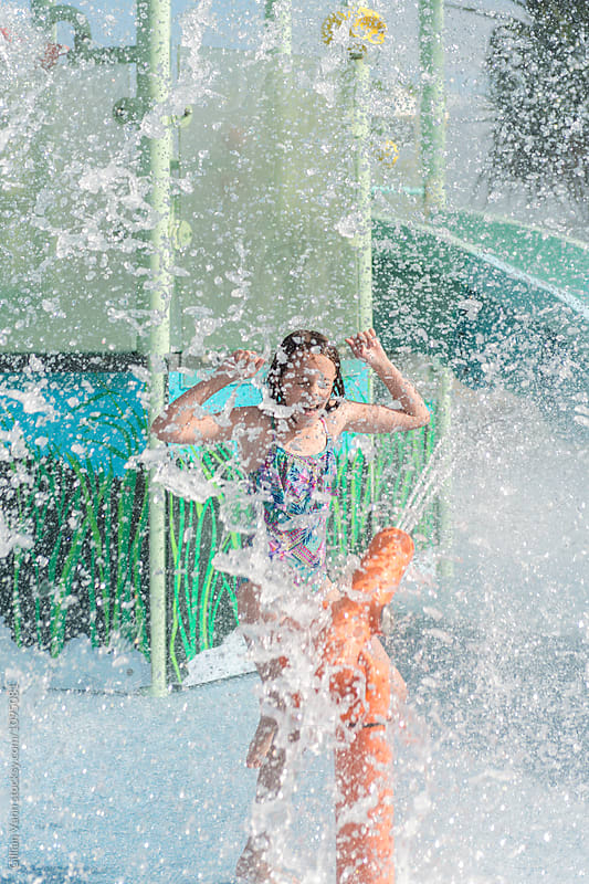 girl at a waterpark being splashed with water under a giant shower by Gillian Vann for Stocksy United