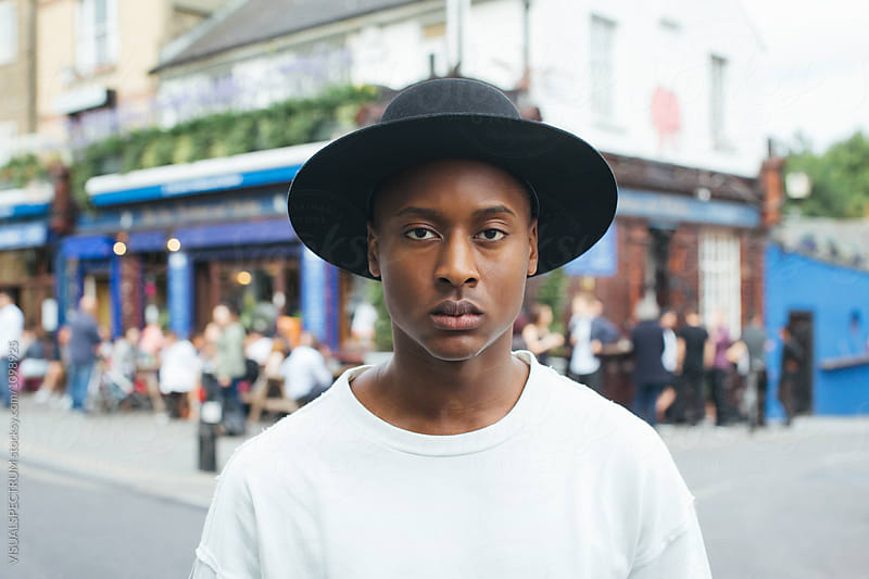 London Street Style - Cool Young Fashionable Black Man Standing in Busy Street by Julien L. Balmer for Stocksy United