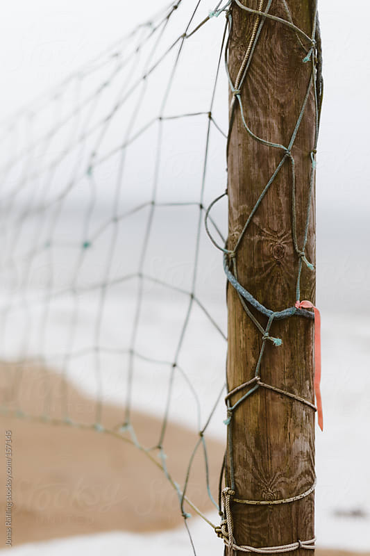 Pole wrapped with fishing net by Jonas Räfling for Stocksy United