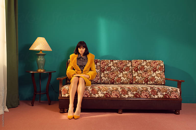 alone lady sitting on a retro couch  by Ulaş and Merve for Stocksy United