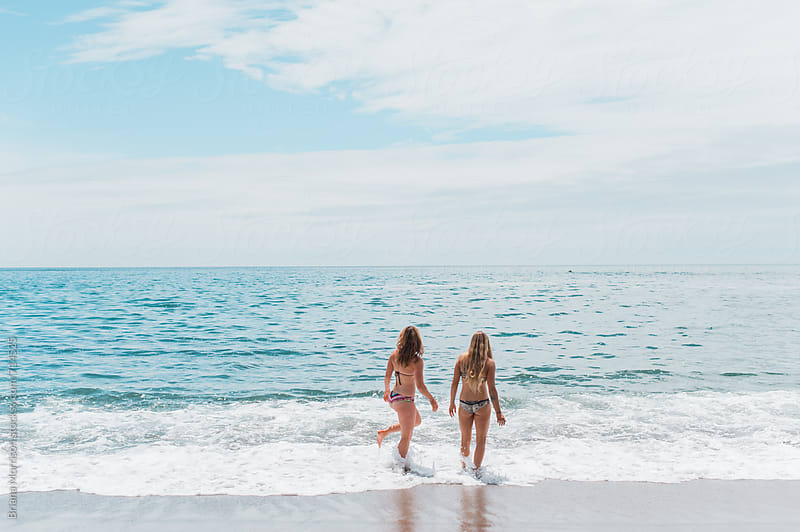 Two Young Women in Bikinis Walking into the Ocean by Briana Morrison for Stocksy United