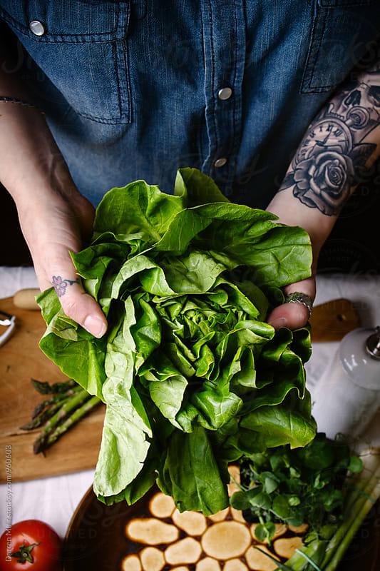 Woman preparing lettuce. by Darren Muir for Stocksy United