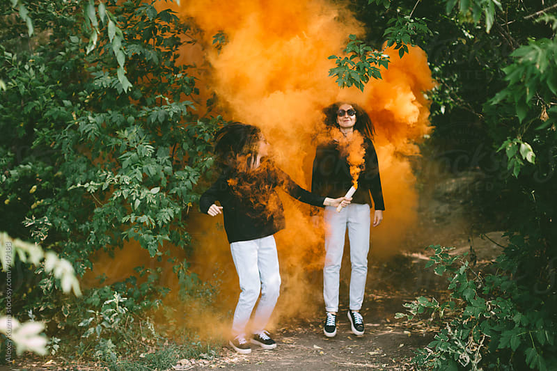 beautiful twins playing with orange smoke bomb by Alexey Kuzma for Stocksy United
