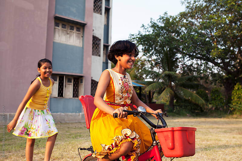 Girls playing with cycle in outdoor by PARTHA PAL for Stocksy United
