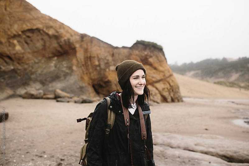 portrait of young woman laughing at beach by Nicole Mason for Stocksy United