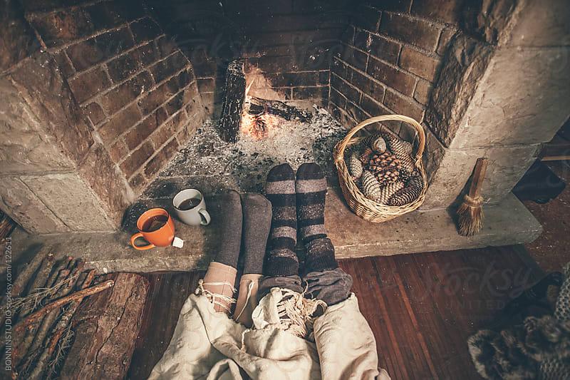 Feet in wool socks warming by cozy fire. by BONNINSTUDIO for Stocksy United