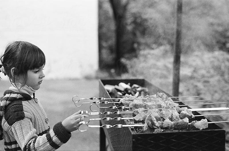 Little girl cooking barbecue by Milles Studio for Stocksy United
