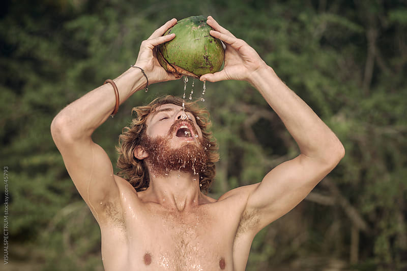 Young Man Drinking Coconut by Julien L. Balmer for Stocksy United