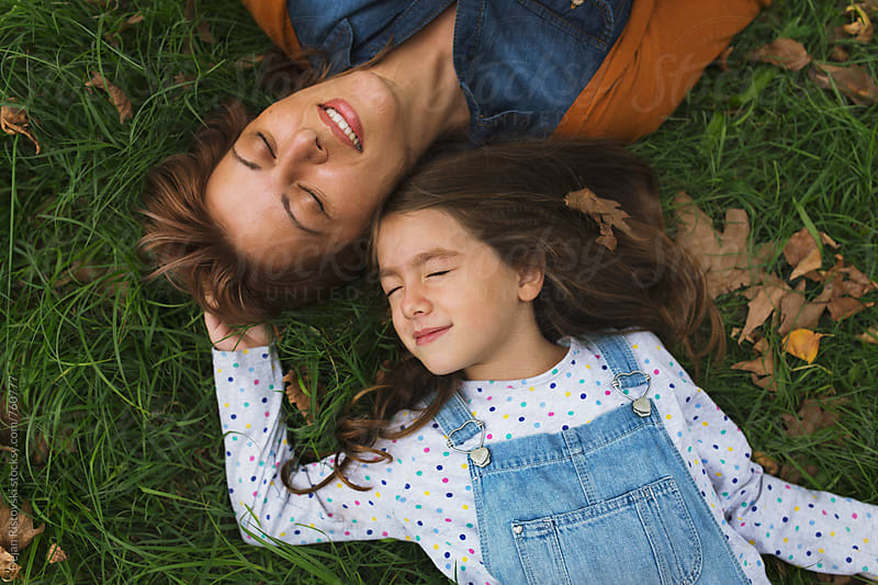 Mother and child lying on the grass by Dejan Ristovski for Stocksy United