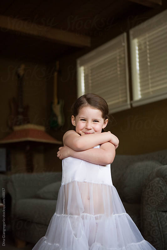 Little girl in white dress / slip folding arms and smiling by Dina Giangregorio for Stocksy United