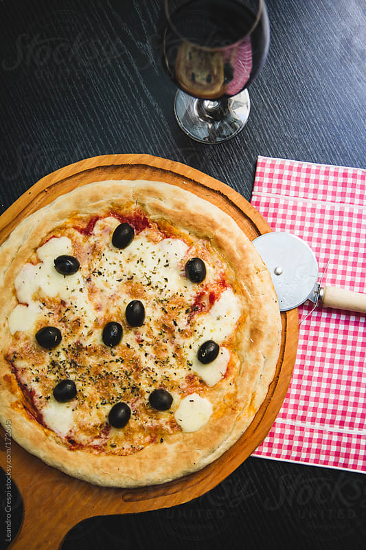 Margherita pizza with black olives by Leandro Crespi for Stocksy United