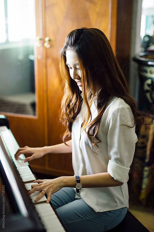 Beautiful woman playing piano at home by Alita Ong for Stocksy United
