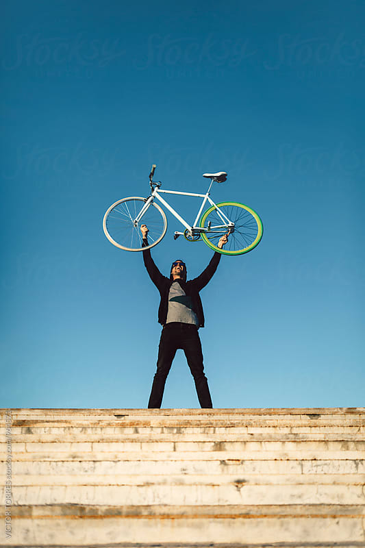 Youn Man with His Bicycle in a Radiant Summer Day by VICTOR TORRES for Stocksy United