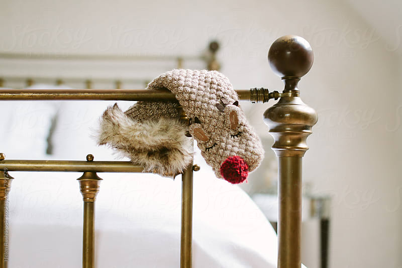 A snuggly Christmas sock draped over the end of a bed. by Helen Rushbrook for Stocksy United