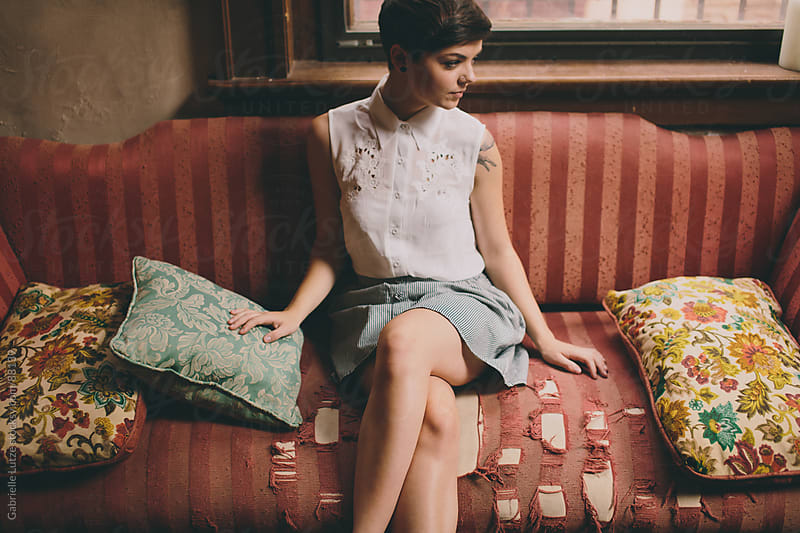 Beautiful girl sitting on vintage couch with pillows by Gabrielle Lutze for Stocksy United