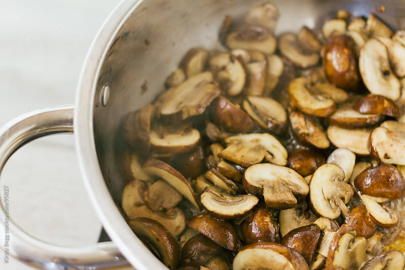 Sliced chestnut mushrooms frying in olive oil and garlic by Kirsty Begg for Stocksy United